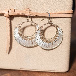 Gold hoop earrings with white string details.